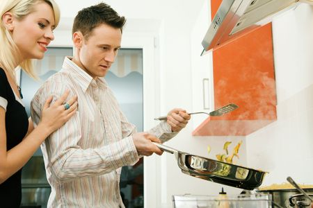 Young couple cooking in their kitchen at home. Selective focus on his face and cooking gear Stock Photo - 6094196
