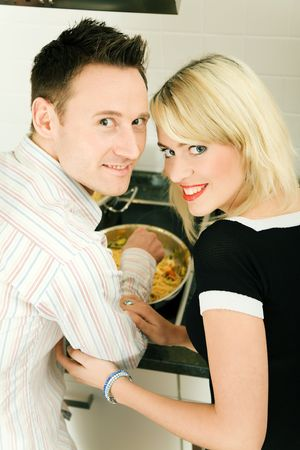 Young couple cooking in their kitchen at home, both looking into the camera Stock Photo - 6094175