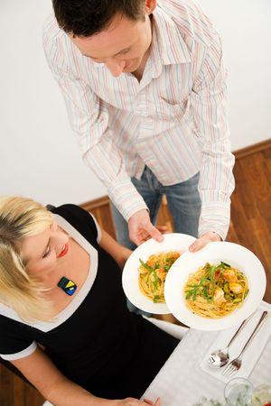 cena romantica: Giovane coppia romantica cena: egli mostra cosa egli ha cucinato - pasta