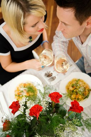 Young couple romantic dinner: letting the white wine glasses clink; focus on the eyes of the people photo