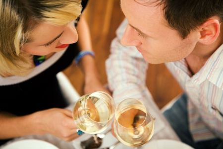 Young couple romantic dinner: clinking the white wine glasses; focus on the eyes of the people photo