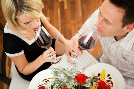Young couple romantic dinner: both drinking red wine and having desert photo