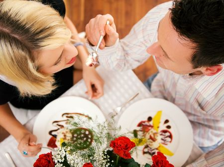 Young couple romantic dinner: he is feeding her with desert (yoghurt mousse); focus on faces photo