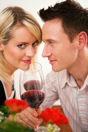 Young couple romantic dinner: clinking glasses with red wine photo