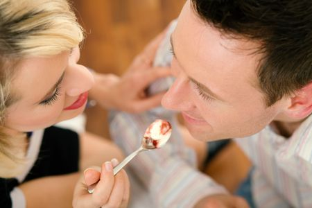 Young couple romantic dinner: she is feeding him with desert (yoghurt mousse); focus on faces photo