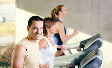 Three people on the treadmill in a gym, young man I front smiling Stock Photo - 6094176