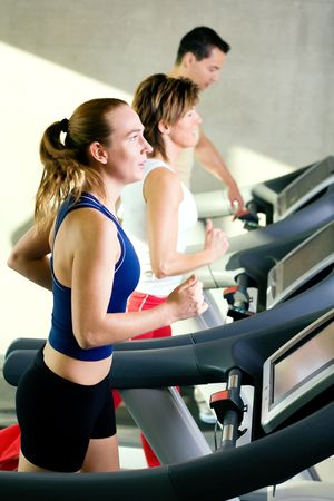 Three rather dynamic people on the treadmill running Stock Photo - 6094179