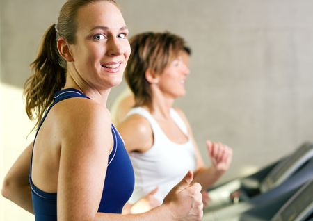 People on the treadmill in the gym, the girl in front smiling Stock Photo - 6094182
