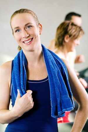 Beautiful girl takes a break from her workout on the treadmill in a gym Stock Photo - 6094160