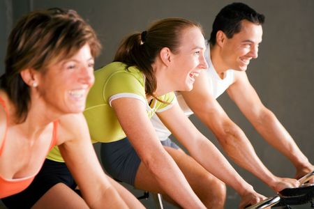 Tree people spinning on stationary bicycles in a gym or fitness club; focus on girl in the middle photo
