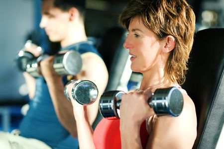 Couple (male / female) exercising with dumbbells in a gym; focus on face of the woman Stock Photo - 6094165