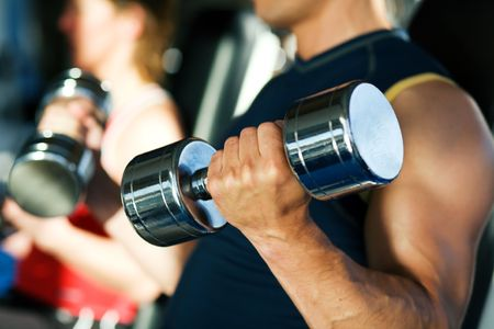uomo palestra: Uomo forte esercizio con dumbbells in una palestra, sullo sfondo di una donna anche sollevamento pesi; concentrarsi sulla mano e manubri Archivio Fotografico