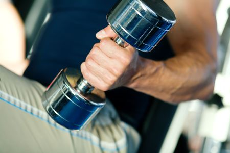 Strong man with dumbbells; focus on hand and dumbbell Stock Photo - 6094188