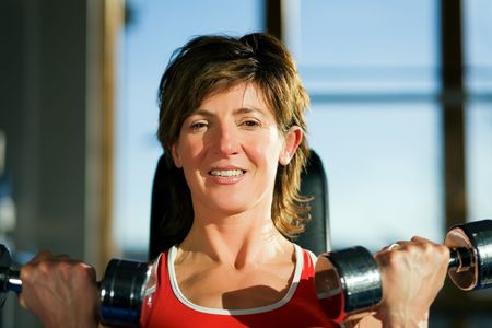 Mature woman lifting dumbbells exercising in a gym; focus on her face photo