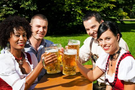 Group of four people in Couple in traditional Bavarian dress, Lederhosen and Dirndl, in a beer garden Stock Photo - 6080709