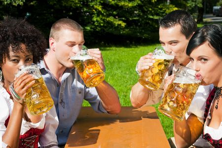Group of four people in Couple in traditional Bavarian dress, Lederhosen and Dirndl, in a beer garden photo