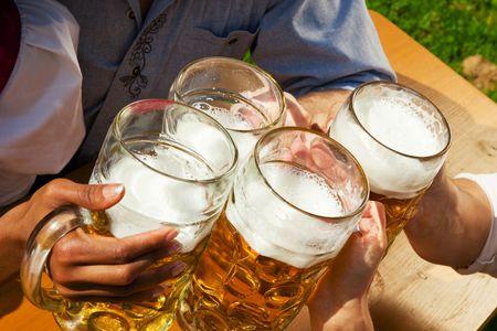 octoberfest: Grupo de cuatro personas en pareja en trajes tradicionales de Baviera, Lederhosen y Dirndl, en un jard�n de la cerveza o en un festival como el Oktoberfest; centrarse en la cerveza steins