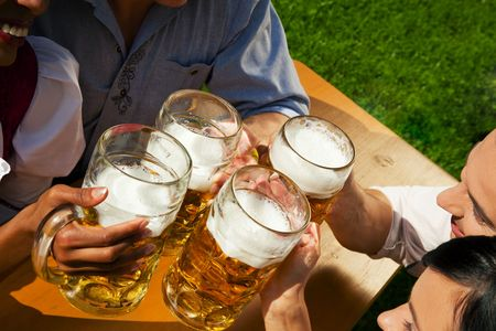 lederhosen: Group of four people in Couple in traditional Bavarian dress, Lederhosen and Dirndl, in a beer garden or at a festival like the Oktoberfest; focus on beer steins