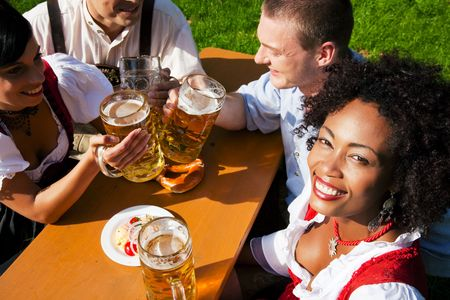 Group of four people in Couple in traditional Bavarian dress, Lederhosen and Dirndl, in a beer garden with Pretzel and Obatzter (traditional cheese) photo