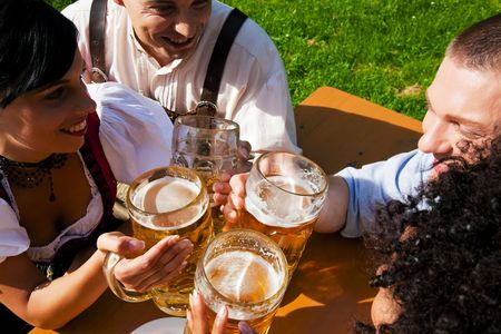 tracht: Group of four people in Couple in traditional Bavarian dress, Lederhosen and Dirndl, in a beer garden