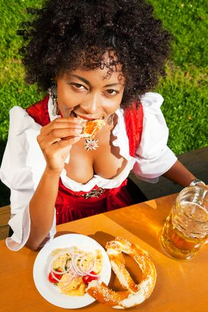 Very beautiful woman of color in traditional Bavarian costume - dirndl - drinking beer and eating pretzel and obatzter (traditional cheese) photo