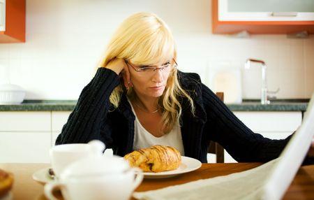 classifieds: Woman having breakfast, reading the classifieds