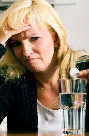 megrim: Woman with a really bad migraine dropping a painkiller pill into a glass of water