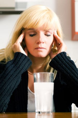 megrim: Woman with a very bad hangover sitting in front of a glass of water with a painkiller