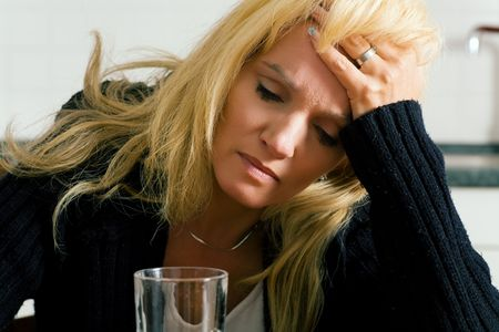 ingest: Very depressed, sad or grumpy looking woman having headache with a glass of water (presumably wit a painkiller in the water)