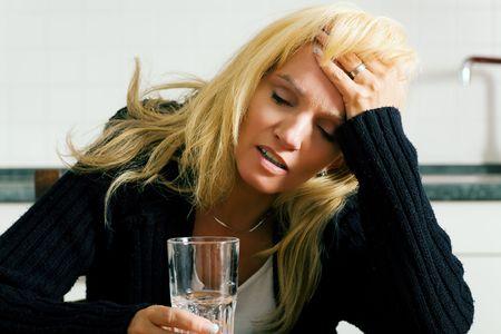 Zeer depressief, verdrietig of chagrijnig ogende vrouw met hoofdpijn met een glas water (vermoedelijk wit een pijnstiller in het water)
