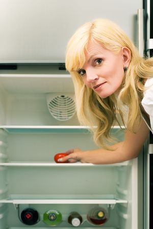 Woman and her fridge: spirits and one tomato photo