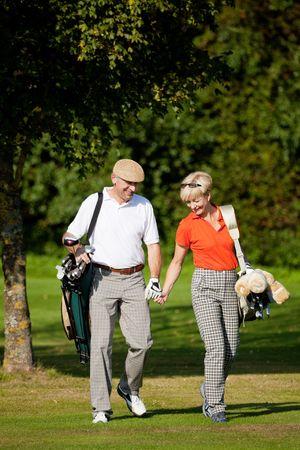seniors walking: Mature or senior couple playing golf, walking down the course Stock Photo
