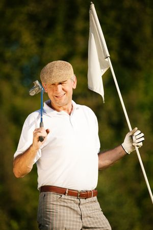 Senior man playing golf holding the flag in his hand Stock Photo - 6092425
