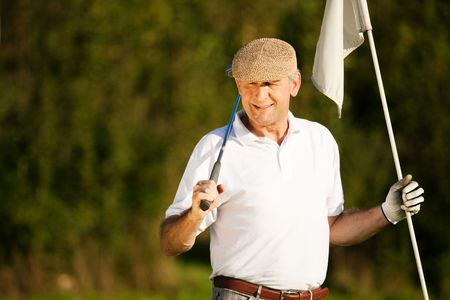 playing golf: Senior man playing golf holding the flag in his hand