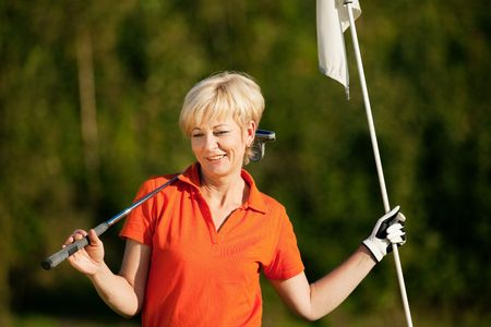Senior woman playing golf holding the flag in her hand Stock Photo - 6081064