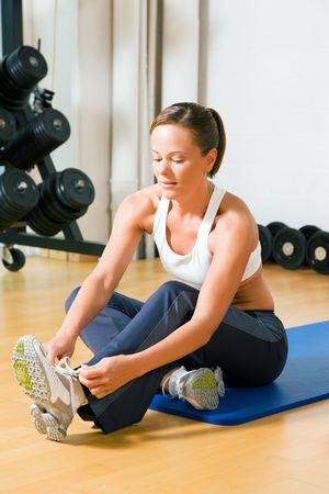 shoelaces: Woman tying her shoelaces before starting her workout in the gym Stock Photo