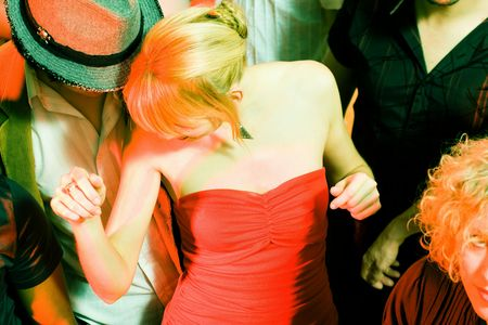 People dancing in a club, a girl in red dress in front photo