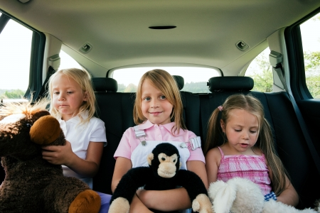 kid sitting: Family with three kids in a car