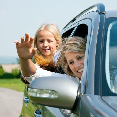 abschied: Familie mit drei Kindern in einem Auto