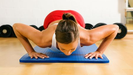Very sportive woman doing pushups in a gym Stock Photo - 6092566