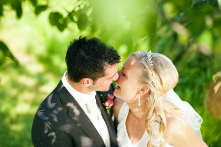 wedding couple hugging and kissing in a private moment of joy photo