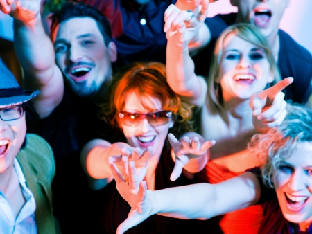 Crowd cheering - their rock idol or simply having fun in a club or disco party (focus on hands!) photo