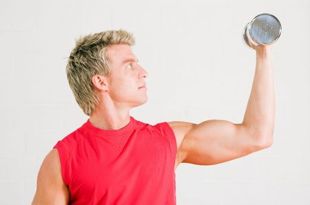 Young sportive man working out using dumbbells in the gym Stock Photo - 6094148
