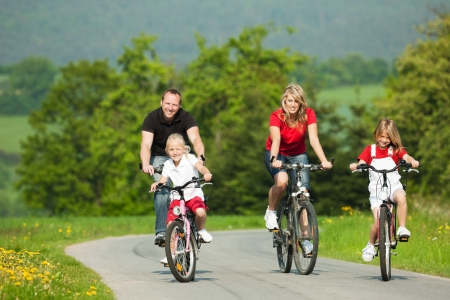 Family with children having a weekend excursion on their bikes on a summer day photo