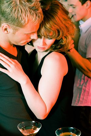 Couple flirting very obviously in a bar or at a club photo