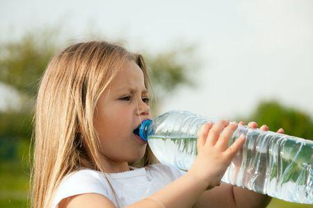 the thirst: bambino assetato di acqua potabile da una bottiglia contro uno sfondo del cielo