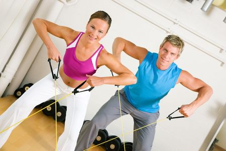 fit couple: Very fit couple in a gym exercising with tube equipment doing power gymnastics