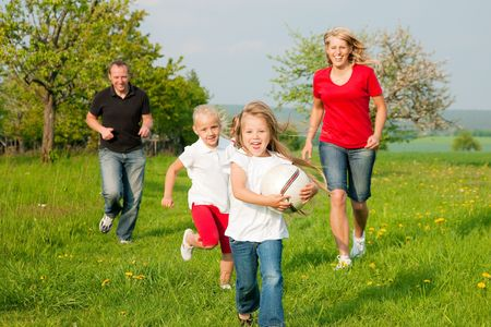 Happy family playing football, one child has grabbed the ball and is being chased by the others Stock Photo - 6117163
