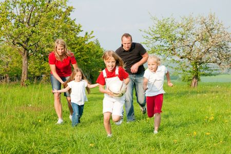 one family: Happy family playing football, one child has grabbed the ball and is being chased by the others Stock Photo