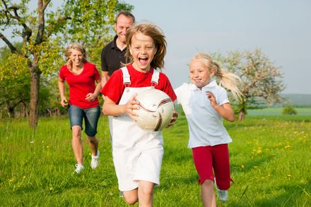 Happy family playing football, one child has grabbed the ball and is being chased by the others Stock Photo - 6117161